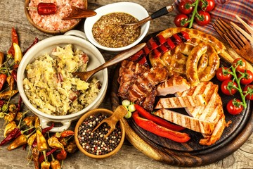 Grilled sausages spiral served on rustic round cutting board with mustard. Homemade barbecue.  Food preparation. Stewed cabbage with meat, mushrooms and sausage.