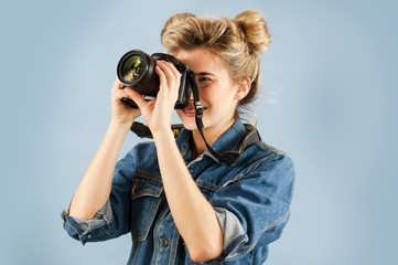 Attractive woman with a photo camera in her hand in the studio on an isolated blue background. The concept of taking pictures and video