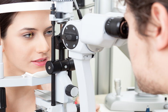 High technology concept health for eyes care - The optician ophthalmology doctor optometrist in the eyes clinic using a binocular slit-lamp to a young woman for an eye control