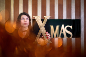 Young woman holding the letter x of the word xmas covered with gold looking up in belief.