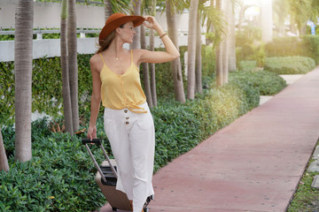 Elegant young woman on vacation walking outdoors with suitcase