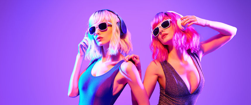 Fashion. Two sexy DJ girl in Colorful neon light dance. Glamour party fitness woman with Dyed Hair in Trendy headphones. Young beautiful model enjoy nightlife. Creative art banner