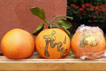 Three fresh grapefruits on a market in Hue, Vietnam for celebration of Vietnamese New Year. The inscription is translated – Hue.