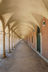 Covered arcade of royal palace at Aranjuez behind fence, Spain