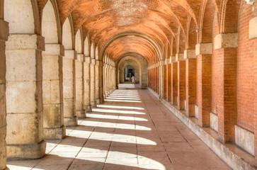Covered arcade of royal palace at Aranjuez behind fence, Spain