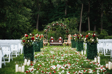 Rose petals cover green garden ready for traditional Hindu wedding ceremony