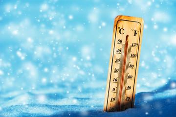 Cold temperature below zero on thermometer in snow