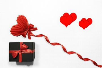 Czerwone serca, czarne pudełko, kokarda i wstążka  w białe kropki na białym tle.