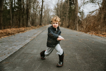 Portrait of boy playing with stick on road