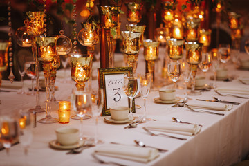 Hindu wedding reception dinner. Tables served with greenery, shiny candles and rose gold decor stands in the restaurant
