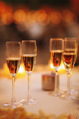 Four glasses with pink champagne stand on the table with shiny candles