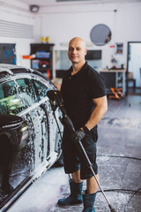 Portrait of confident male worker holding hose while standing by car in workshop