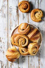 Variety of homemade puff pastry buns cinnamon rolls and croissant in ceramic plate over white plank wooden background. Flat lay, space