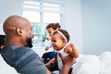 Happy father playing with children while relaxing on bed at home