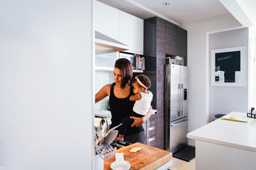 Mother carrying cute daughter while standing in kitchen at home