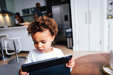 Close-up of cute boy using tablet computer while standing against family at home