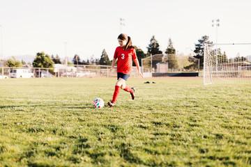 Full length of girl wearing uniform kicking soccer ball on field