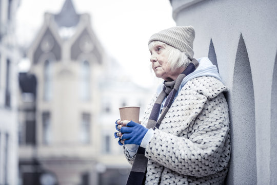 Sad aged woman standing at the corner of a building
