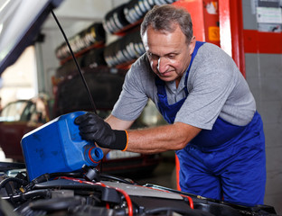 Mechanic engaged in replacement of engine oil