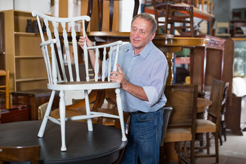 Man with wife are choosing old antique chair in shop