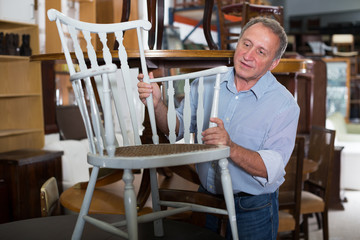 Smiling adult man is buying antique armchair