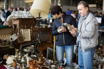 Loving mature couple choosing vintage goods