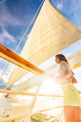 Wall Mural - Luxury travel elegant woman on cruise ship yacht on jet set vacation sailing around the world. High end tourism sail boat in sunset.