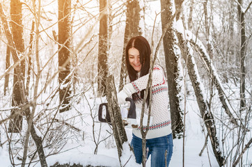 Woman in a white sweater cuts dry branch tree with a chain saw in the forest. Deforestation, sawing, lumberjack and forestry equipment