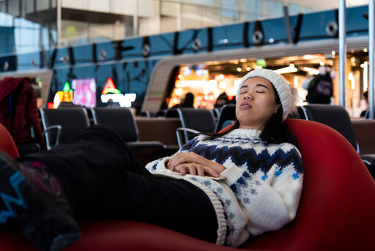 Girl taking a nap while waiting at the airport