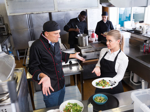 Waitress with dish talking with puzzled chef