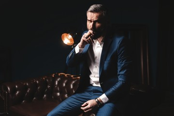 Handsome rich man is relaxing on the leather sofa and smoking expensive cigar.