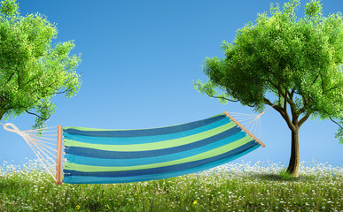 a relaxing on hammock in backyard in spring flowers and grass garden