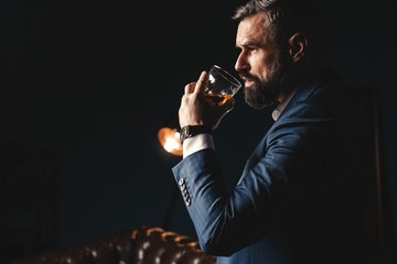 Degustation, tasting. Man with beard holds glass of brandy. Tasting and degustation concept. Bearded businessman in elegant suit with glass of whiskey