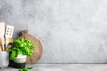 Kitchen shelf. Appliances for the kitchen in a gray modern stand, basil in a gray mug on the background of a gray concrete wall. Horizontal, space.