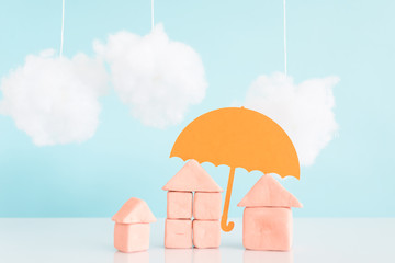 an umbrella over a house,concept of security and insurance of property