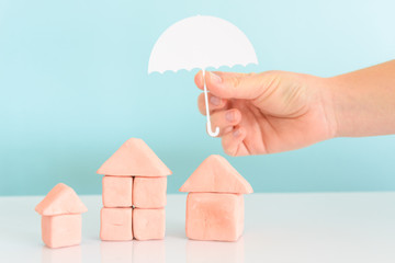 Hand holding an umbrella over a house,concept of security and insurance of property