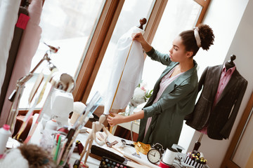 Wall Mural - Young designer with tape is measuring white shirt. Designers studio