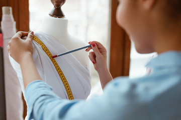 Wall Mural - Young designer with tape is measuring white dress. Designers studio