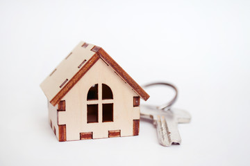 Wooden house with key on white background, concept for selling houses with copyspace