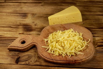 Grated cheese on cutting board on wooden table