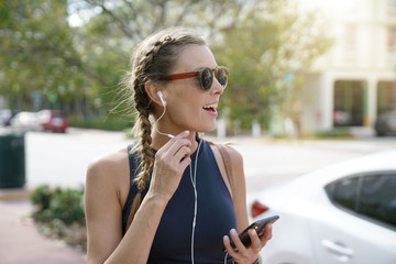 Attractive young woman in sportswear talking on cellphone with headphones