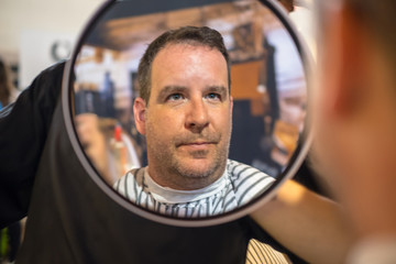 A happy guy is checking his fresh new haircut in a mirror at the hairdresser