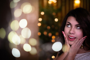 Beautiful young woman in front of christmas tree looking up in belief.
