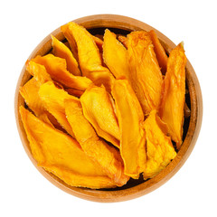 Dried mango strips in wooden bowl. Sliced, dehydrated mangoes. Juicy tropical stone fruit with yellow and orange color. Mangifera. Isolated macro food photo, closeup, from above, on white background.
