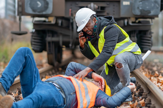 Railroad engineer injured in an accident at work on the railway tracks. Calling for help