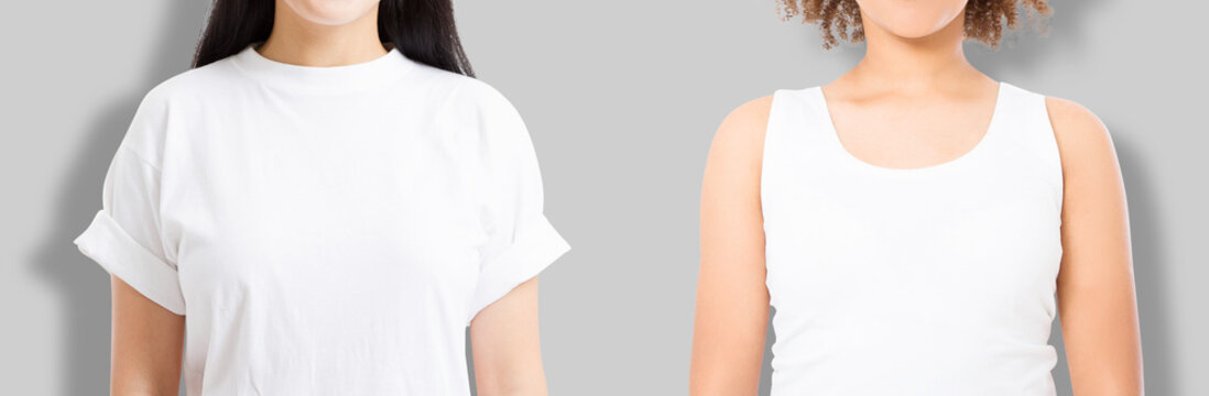 Asian and african american girl in blank template t shirt isolated on gray background. Women in tshirt with copy space and mock up for advertising. White shirts. Front view. Cropped image