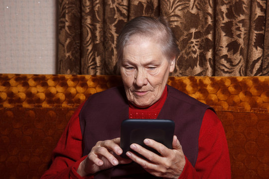 Old woman reading ebook on digital tablet device sitting in her sofa