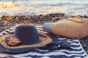 Accessories for relaxing on the beach, sun protection in the summer, sunglasses, straw hat, beach towel, seashell. Blue ocean in the background in the sunlight.