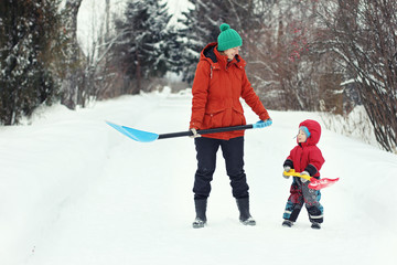 Young mother and her toddler son stand with snow shovels on rural road. Winter seasonal concept