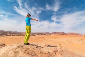Young girl above desert pointing to red sand dunes, Wadi Rum, Jordan